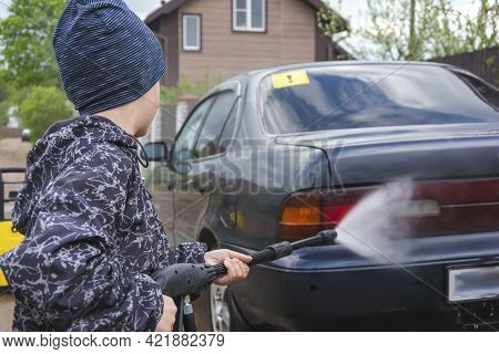 The Child Washes The Car With A High-pressure Washer, The Son Helps The Father To Wash The Car, High