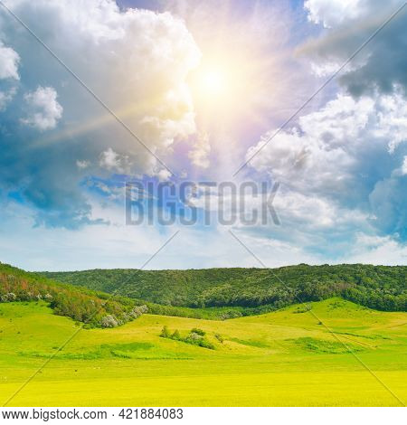 Vast Grassy Meadow With Distant Hills, Trees And Cloudy Sky