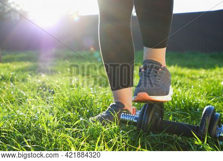 A Woman Ties Her Laces On Her Running Shoes Before Jogging. View In The Backlight Of The Setting Sun