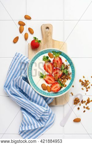 Greek Yogurt In White Bowl With Ingredients For Making Breakfast Granola And Fresh Strawberries On W