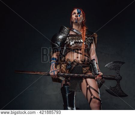Mediaeval Woman Viking Posing In Dark Background With An Axe