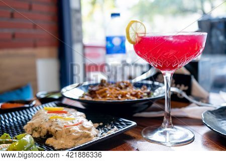 Table Full Of Street Fast Fusion Food And Tall Glass Filled With Pink Red Drink Of Strawberry Cherry