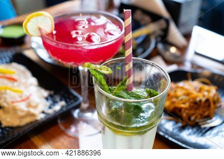 Close Up Shot Of Red Pink Colored Drink Made Of Strawberry Cherry And Berries And Mojito With A Lime