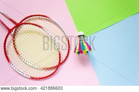 Rackets And A Badminton Shuttlecock On A Multicolored Background, Top View. Sports, Summer Outdoor A