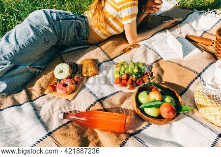 Fresh Fruits And Berries, Drinks And Bakery On Picnic Blanket Outdoor, Summer Vacation, Woman Lying