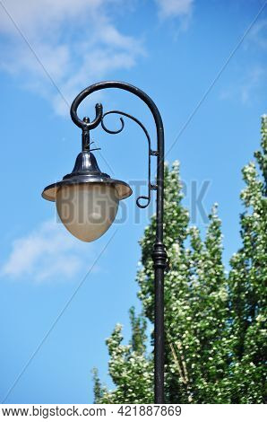 Lantern, City Lighting. Lantern On A Background Of Blue Sky And Green Trees.