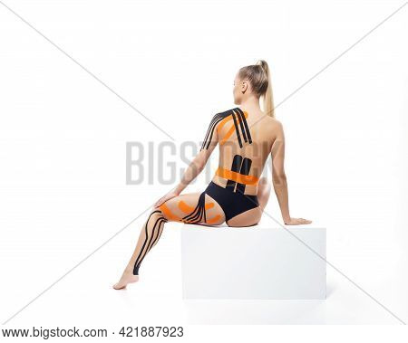 Physio Tapes Applied To The Body Of A Young Athletic Woman Isolated On White Background. Physiothera