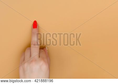Hand Of Caucasian Young Woman Pointing Up Middle Finger With Red Nail On Pastel Peachy Background. G