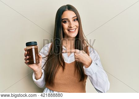 Beautiful brunette young woman holding soluble coffee smiling happy pointing with hand and finger