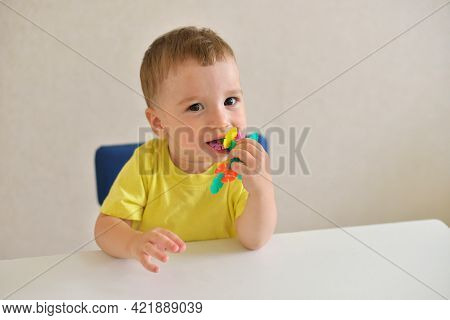 Toddler Boy Plays Constructor While Sitting At A White Table. Educational Game Montessori Fine Motor