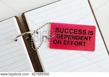 Business Concept. Red Notebook With Text Success Is Dependent On Effort