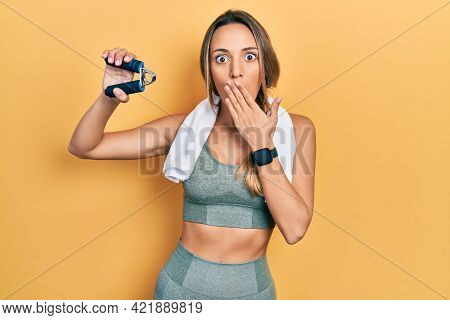 Beautiful hispanic woman training muscle with hand grip covering mouth with hand, shocked and afraid for mistake. surprised expression