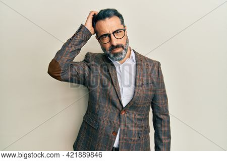 Middle age man with beard and grey hair wearing business jacket and glasses confuse and wonder about question. uncertain with doubt, thinking with hand on head. pensive concept.