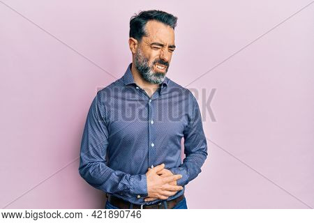 Middle age man with beard and grey hair wearing business clothes with hand on stomach because nausea, painful disease feeling unwell. ache concept.