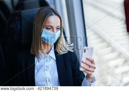 Subway commuter businesswoman in mask on public transport using smartphone