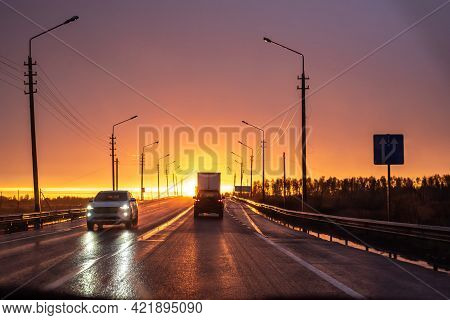 Driving Along Modern Road With Automobiles Past High Streetlights At Picturesque Golden Sunset Light