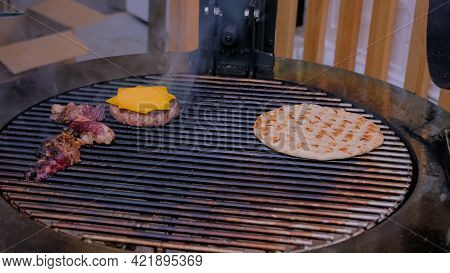 Process Of Cooking Pieces Of Meat, Buns, Cutlet With Cheese For Burgers And Pita On Grill At Summer