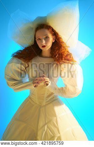 Fashion art. Portrait of a sophisticated fashion model girl with lush red curly hair posing in a white haute couture dress and a huge bow. Studio portrait.