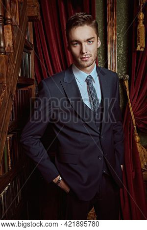 Men's beauty, fashion. Portrait of a handsome young man in a formal suit posing in a luxury apartments with classic interior.