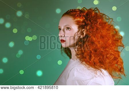 Hairstyling and makeup. Portrait of a refined fashion model girl with lush red curly hair posing in a white haute couture dress on a green background with lights.