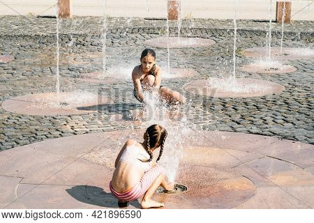 A Girl Plays With A Street Fountain On A Summer Day. Hot Summer Sunny Day.two Little Girls Sisters S