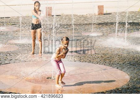 Hot Summer Sunny Day.two Little Girls Sisters Splashing In The Fountain On A Summer Day. Summer Heat