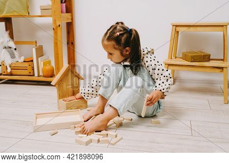 The Girl Sits On The Floor And Builds A Tower Out Of The Constructor.