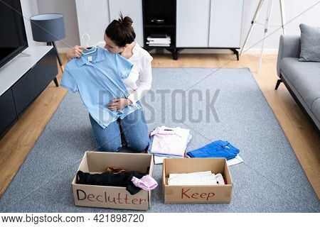 Woman Decluttering Clothes, Sorting And Cleaning Up