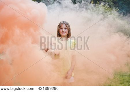 A Girl With A Short Haircut Stands In The Colored Smoke And Looks At The Camera.