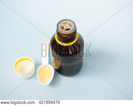 The Concept Of Health Care, Treatment And Medicine - A Bottle Of Medicines Or Antipyretic Syrup And