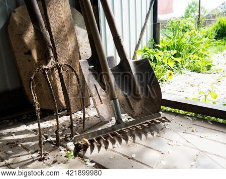 Old Garden Tools, Shovel, Fork And Rake Are In The Shed, The Concept Of Garden Tools.