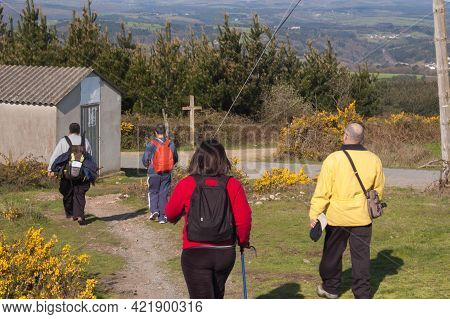 Group Of Four Adult People Following The Santiago Way Near Coruña, Spain