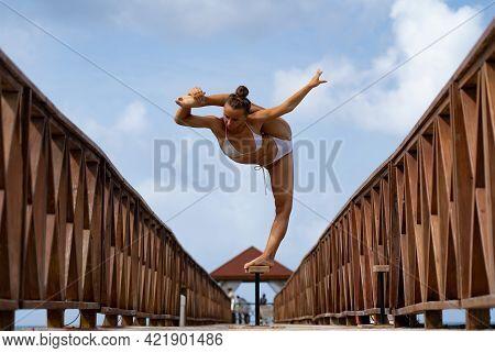 Flexible Female Circus Artist Keep Balance In Split On The Bridge. Healthy Lifestyle, Yoga And Flexi