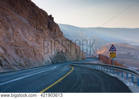 Road In The Negev Desert In Israel. Two-lane Desert Highway. Road Signs Slow In English, Arabic And