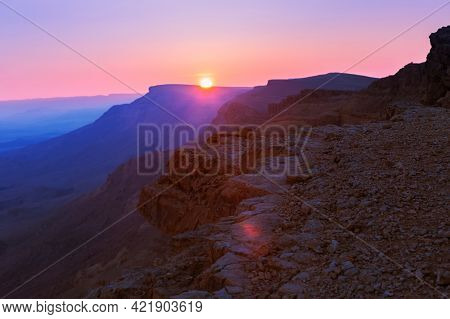 Stunning Sunset In The Mountains. Bright Backlit Sky And Clouds. Silhouettes Of Mountain Peaks In Th