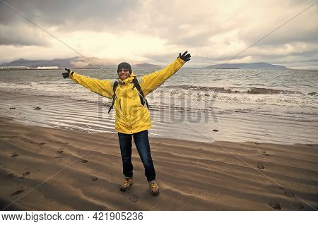 Happy Man On Sea Beach In Reykjavik, Iceland. Man Traveler Smile With Raised Arms On Sea Shore. Free