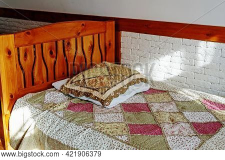 Antique Wooden Bed With Decorated Blanket And Small Pillows Near White Wall At Sunbeam In Room Of Co