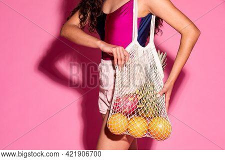 Beautiful woman using a net bag when buy fruits