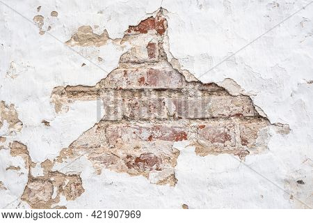 Wall Of Old Destroyed Building Made Of Red Bricks With Large Hole In Chipped White Stucco On Street
