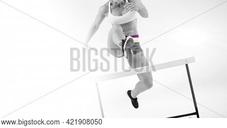 Composition of female athlete hurdle jumping with copy space on white background. sports and competition concept digitally generated image.