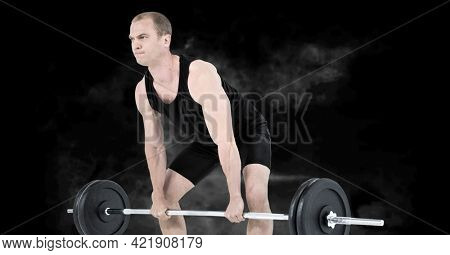 Composition of caucasian male weightlifter with barbell with smoke on black background. sports and competition concept digitally generated image.