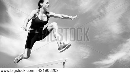 Composition of female hurdle jumper with copy space in black and white. sport and competition concept digitally generated image.