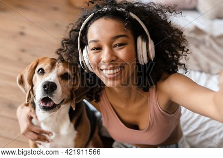 Young african woman in casual wear with beagle puppy at home, relaxing on bed in headphones, taking a selfie