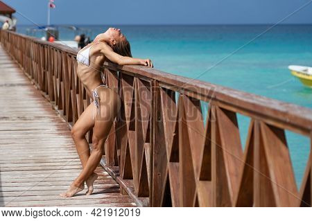 Beautiful Woman Posing On A Pier With Blue Water In A White Bikini. Vacation And Travel Concept.