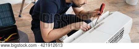 Cropped View Of Bearded Handyman Holding Screwdriver While Fixing Broken Air Conditioner, Banner.