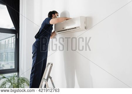 Repairman In Medical Mask Standing On Ladder And Fixing Air Conditioner.