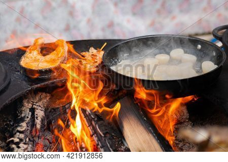 Process Of Cooking Scallop Meat, Salmon, Prawn On Black Brazier At Summer Outdoor Food Market: Close