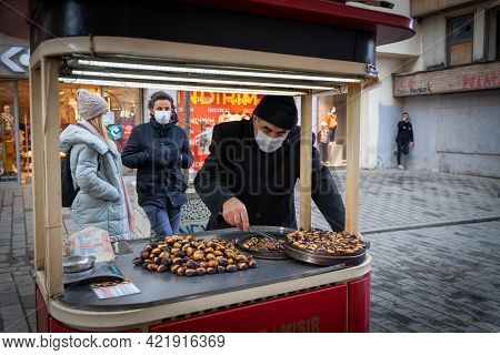 Turkey Istanbul 2021-03-05 Seller Of Traditional Street Food Fried Chestnut And Protective Face Mask