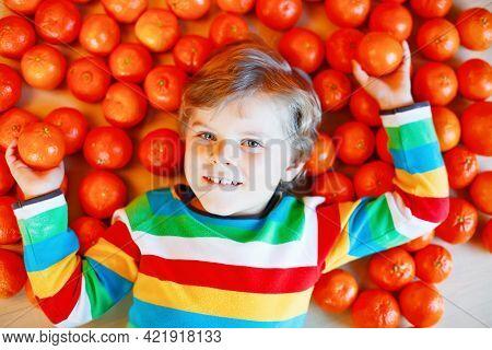Adorable Little Kid Boy With Mandarin Tangerine Oranges Background. Happy Smiling Child Having Fun W