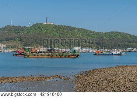 Sinjindo, South Korea; May 5, 2021: Barges With Industrial Crane On Water In Small Seaport.